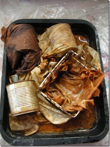 rusty baking tray with fabric, water and lots of objects in it