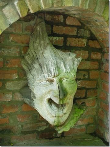 wooden sculpture of creature's head