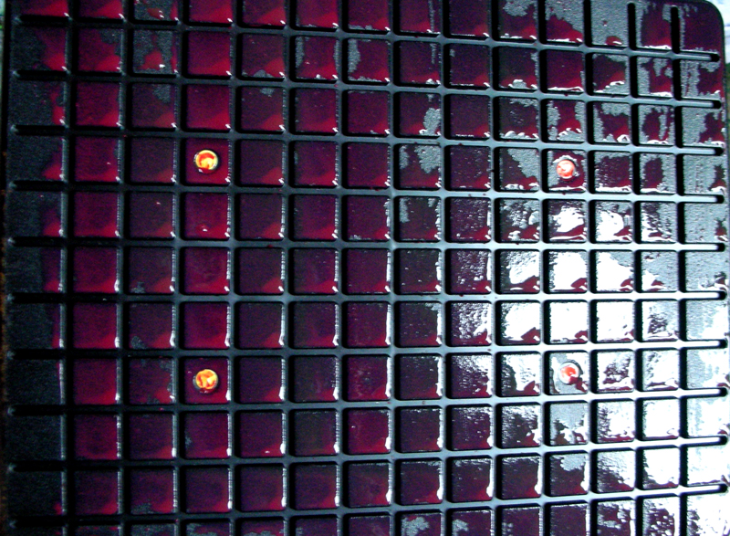 black plastic grid painted with red paint