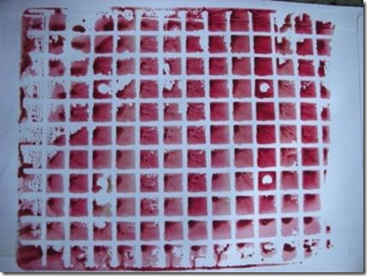 red paint printed on to envelope from grid