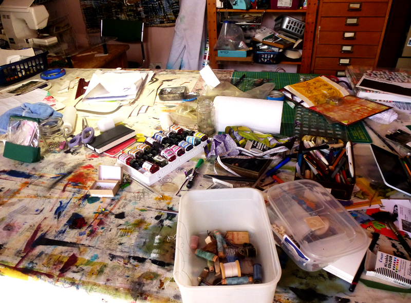 messy studio with pens and inks all over the table