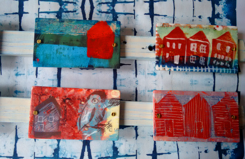 ceramic doorplates with images of beach huts, screwed to wooden batons